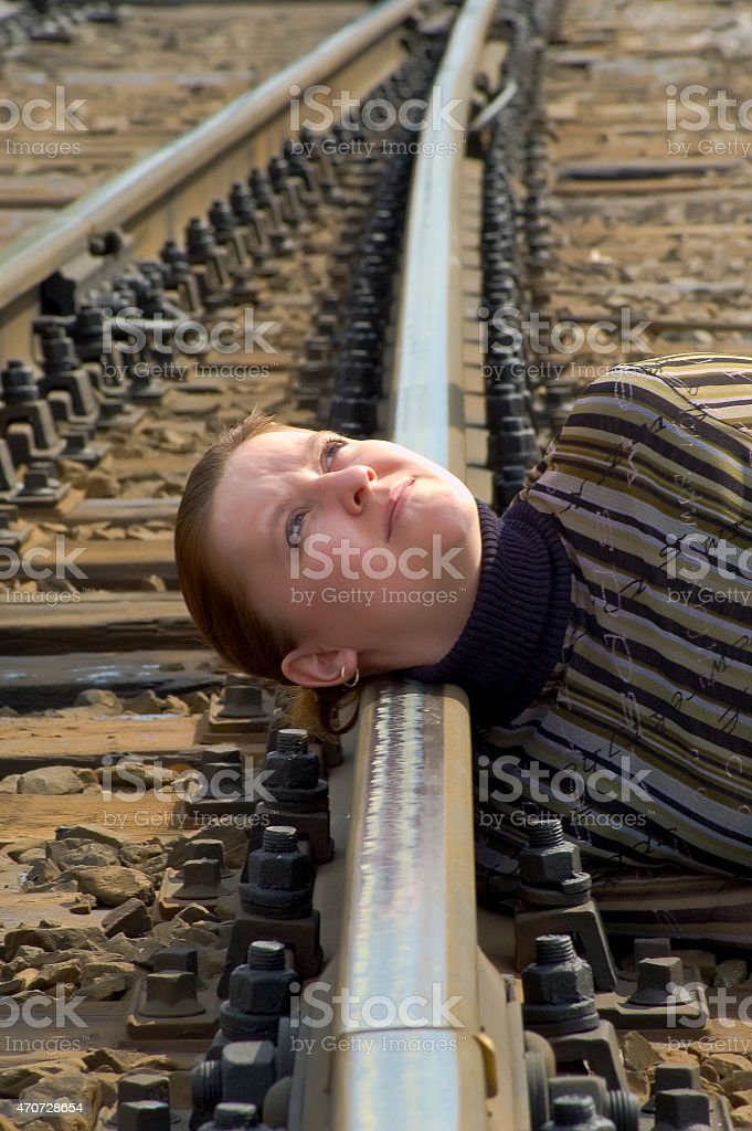 Depressed young woman tries to commit suicide on railway stock photo
