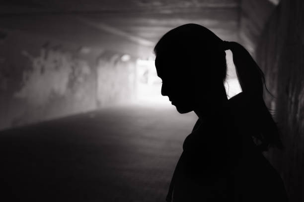 Depressed young women in the tunnel Depressed sad young female standing in a dark tunnel suicide stock pictures, royalty-free photos & images