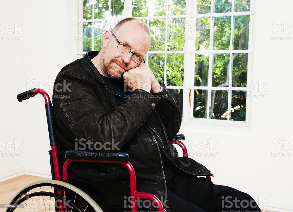 Depressed-looking mature man sitting in wheelchair against window stock photo