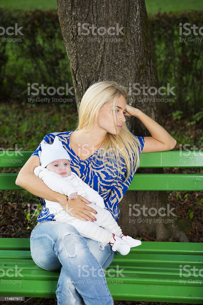 Depressing single mother and her baby sitting on a bench royalty-free stock photo
