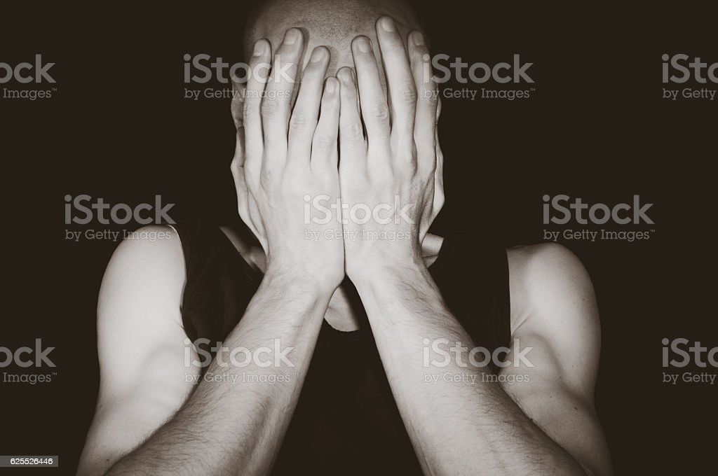 Depression. Depressed man cover his face with his hands. Isolated...