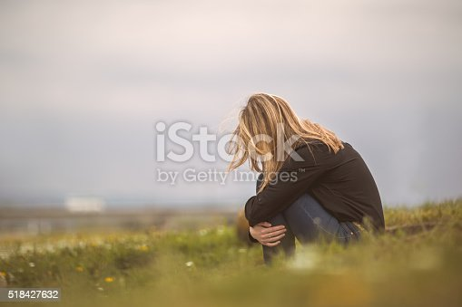 Side view of a despaired woman sitting curled up in nature.