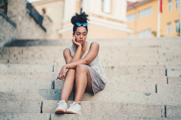 Depression in young people Unhappy young girl sitting at the steps outside low self esteem stock pictures, royalty-free photos & images