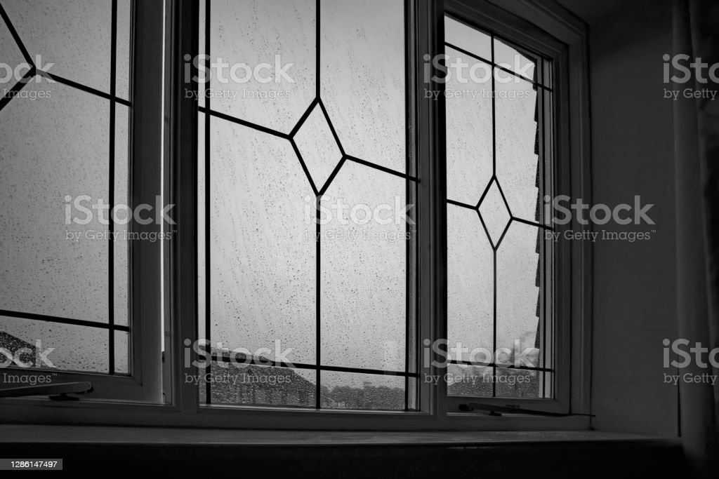Depression Wet and windy day viewed through a suburban window and expressing the depression and helplessness of unemployment and lock down. 2020 Stock Photo