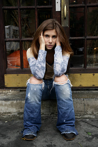 Depression Homeless or depressed girl sitting on the sidewalk  absentee stock pictures, royalty-free photos & images