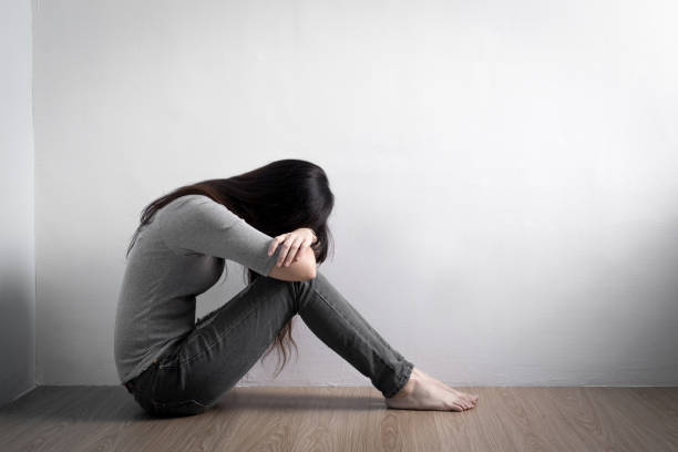 床の上にうつ病の女性座る - 女性 落ち込む ストックフォトと画像
