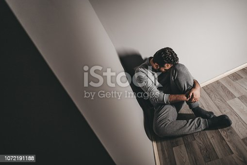 Young depressed man sitting on floor