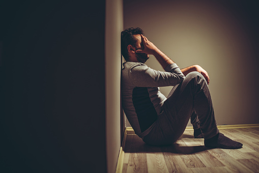 Young depressed man sitting on floor.