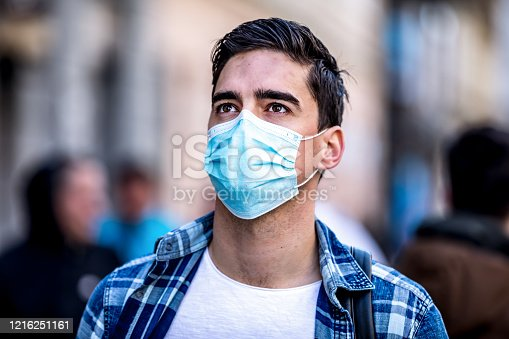 Concept, diseases, viruses, allergies, air pollution. Portrait of young man wearing a protective mask, walking in the city.The image face of a young man wearing a mask to prevent germs, toxic fumes, and dust. Prevention of bacterial infection Corona virus or Covid 19 in the air around the streets and gardens.