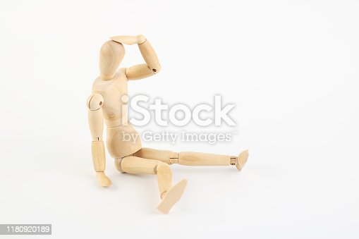 Depressive or exhausted Wooden mannequin sitting on bottom