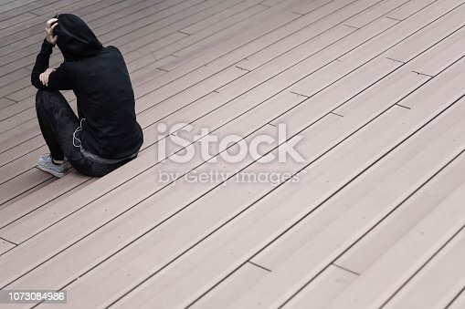 istock Depressive woman sitting on the stairs outdoors 1073084986