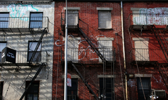 derelict apartments with a for sale sign . new york city