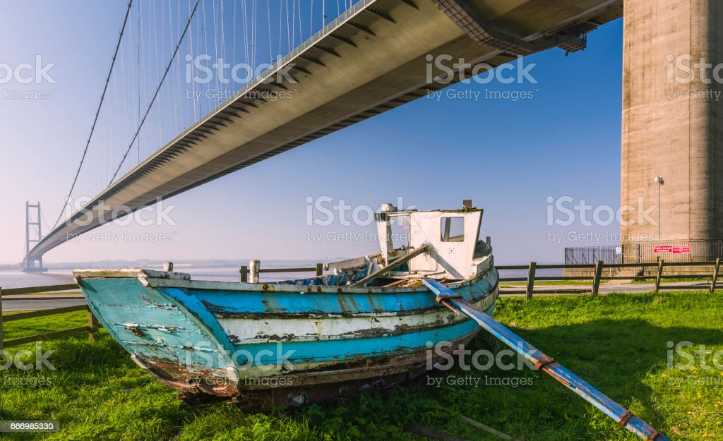 Derelict boat under Humber Bridge in spring. stock photo