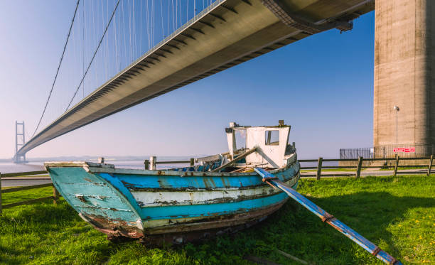 derelict boat under humber bridge in spring. - hull stock pictures, royalty-free photos & images