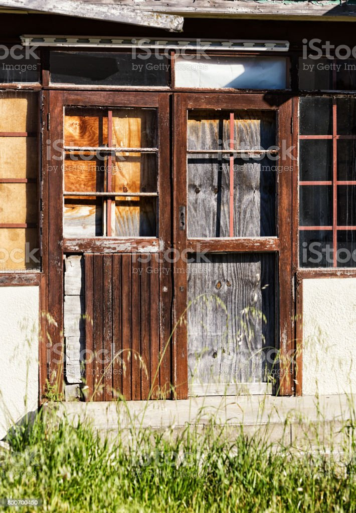 Derelict building boarded up and falling down stock photo