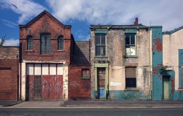 derelict houses and abandoned commercial property on a residential street with boarded up windows and decaying crumbling walls stock photo