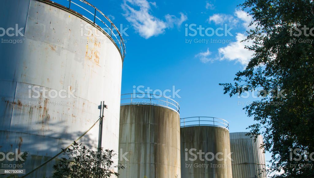 derelict industrial tanks overgrown with weeds and rusty stock photo