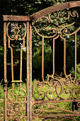 Derelict ornate wrought iron gate in a woodland
