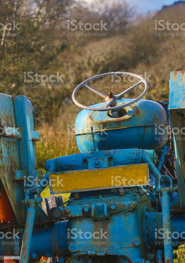 Derelict tractor rotting in a field steering wheel still intact royalty-free stock photo