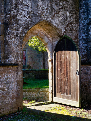 In the ruins of a medieval church the open door lets in the winter sunlight