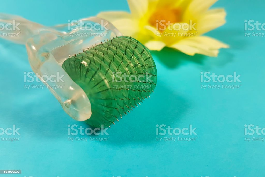 Derma roller for medical micro-acupuncture skin rejuvenation flower in the background stock photo