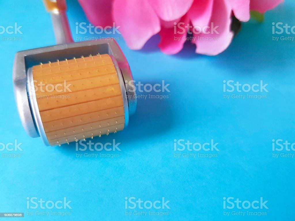 dermaroller, mesoroller for skin flower, color background stock photo