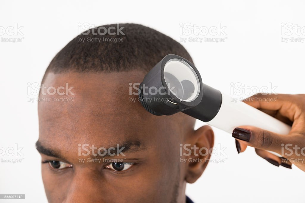 Dermatologist Checking Mole On Man In Clinic stock photo