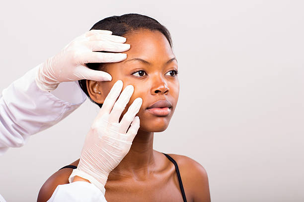 dermatologist checking young african american woman face skin stock photo