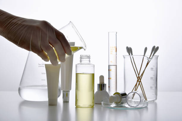 Dermatologist formulating and mixing pharmaceutical skincare, Cosmetic bottle containers and scientific glassware, Research and develop beauty product concept. stock photo
