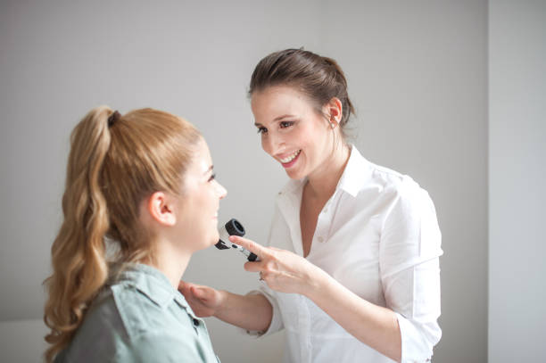 dermatologist inspecting patient face skin with dermatoscope - dermatologist stock pictures, royalty-free photos & images