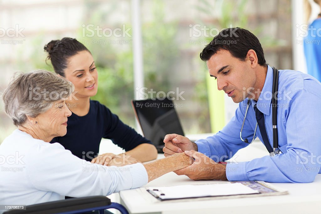 dermatologist inspecting senior patient skin stock photo