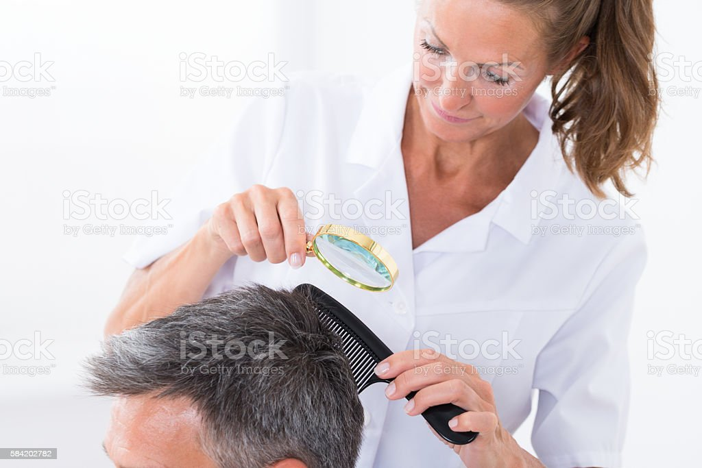 Dermatologist Looking At Patient's Hair stock photo