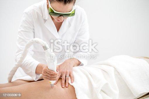Dermatologist Removing Vascular Veins on Woman's Leg with Laser Treatment