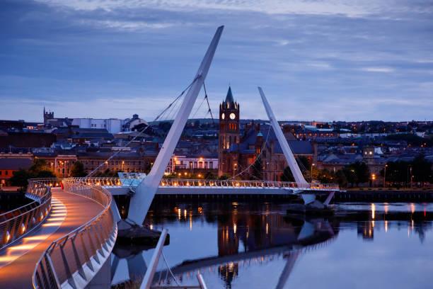 Derry, Irland. Illuminated Peace Bridge in Derry Londonderry, City of Culture, in Nordirland mit Stadtzentrum im Hintergrund. Nachtwolkenhimmel mit Reflexion im Fluss in der Dämmerung – Foto