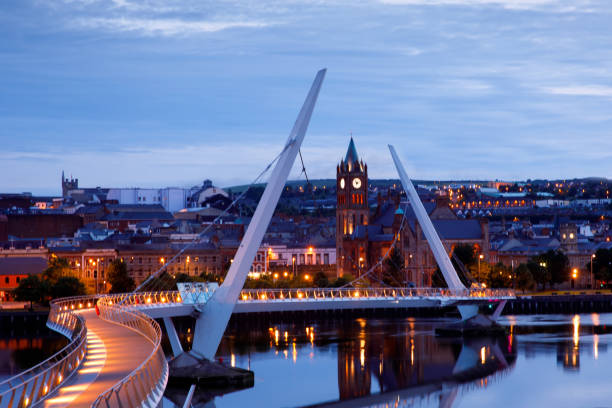 Derry, Ireland. Illuminated Peace bridge in Derry Londonderry, City of Culture, in Northern Ireland with city center at the background. Night cloudy sky with reflection in the river at the dusk stock photo