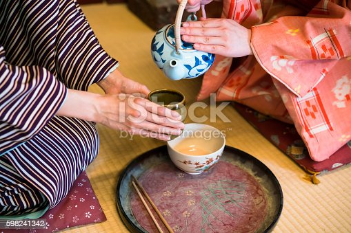 detail of two women in traditional kimono, kneeling on tatami preparing, pouring a  cup of tea which is inthe hands of one woman. They are in traditional Japanese old house on tatami. This is in Toei studios in Kyoto with old buildings from Samurai times.