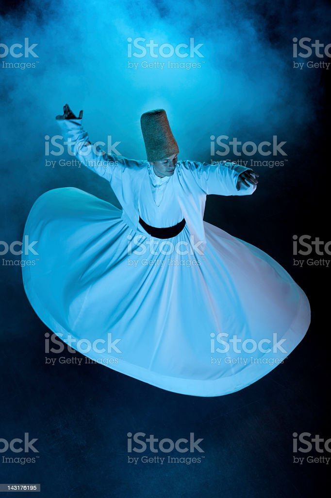 Dervish spinning in white from above on black background stock photo