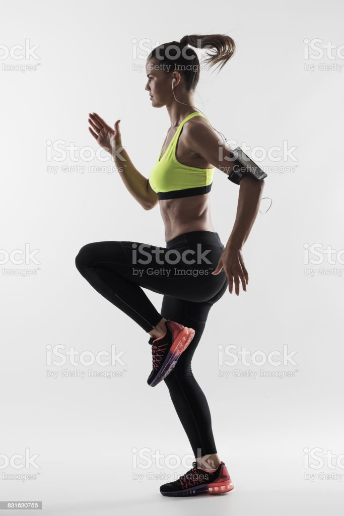Desaturated back lit silhouette of athletic woman runner motion while sprinting fast stock photo