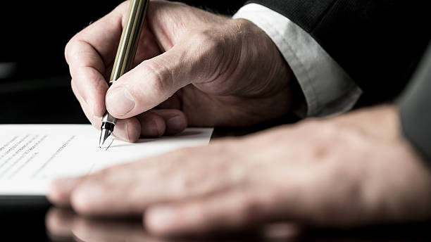 Desaturated image of signing a contract Desaturated image of the hands of a businessman signing a contract with a fountain pen. desaturated stock pictures, royalty-free photos & images