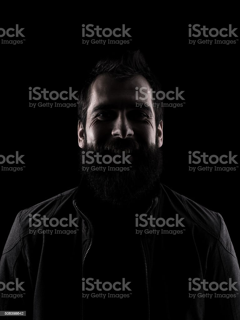 Desaturated laughing mysterious man looking at camera stock photo