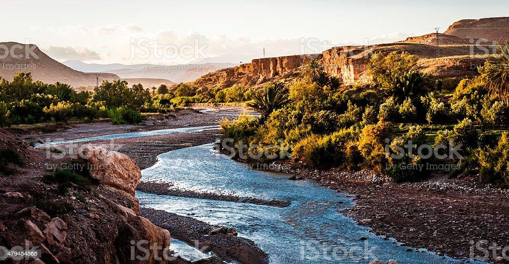 Desert Cliffs rise from a Desert River in Morocco stock photo