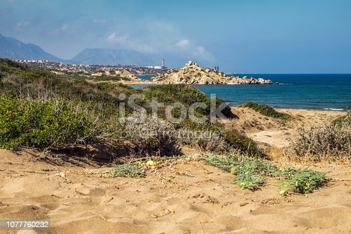 istock Desert coastline with sand Alagadi beach of Northern Cyprus and factory and mountains on horizon 1077760232