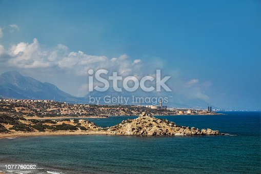 istock Desert coastline with sand Alagadi beach of Northern Cyprus and factory and mountains on horizon 1077760262