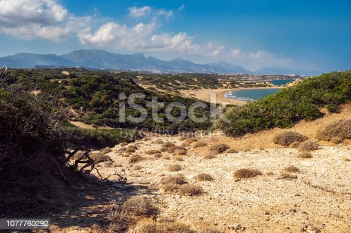 istock Desert coastline with sand Alagadi beach of Northern Cyprus and factory and mountains on horizon 1077760292