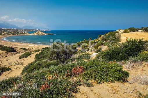 istock Desert coastline with sand Alagadi beach of Northern Cyprus and factory and mountains on horizon 1077760296