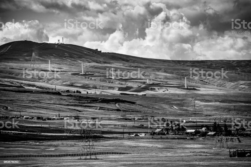 Desert Farm Scene in black and white hill with clouds and construction stock photo
