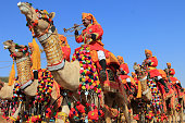Jaisalmer, India - February 01:Traditionally dressed border security people ride camels to attend a cultural procession for the Desert festival held in Jaisalmer, Rajasthan, India.