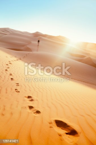Male hiker from behind, walking across sand dunes in the desert towards the sunset, leaving trails / footprints in the sand.