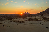 Desert landscape with silhouettes of eroded granite rock formations at sunset
