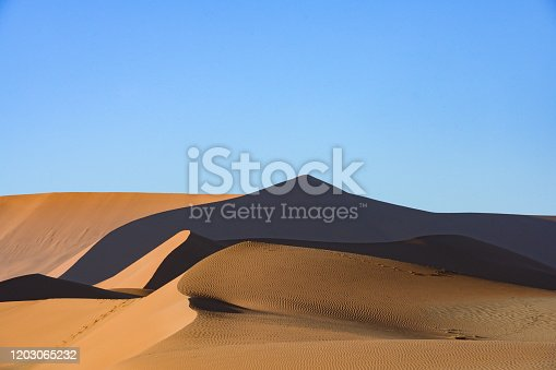 This is a landscape photograph of sand dunes in Sossusvlei National Park in  Nambia Africa with a clear blue sky.